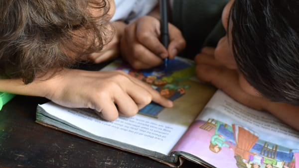school kids writing in book